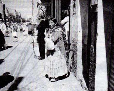 Foto de mujer indígena en la vereda de una calle de una ciudad, foto de semanario Acción Informativa